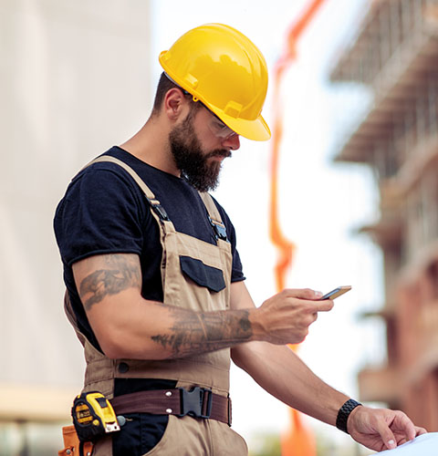 Construction worker with tattoos and yellow hard hat onsite looking at mobile cell phone
