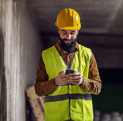 Construction worker on site wearing yellow hard hat and hi-vis vest holding a mobile phone