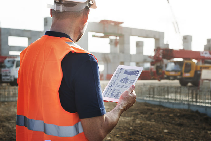 Construction worker with orange hi-vis vest onsite holding tablet