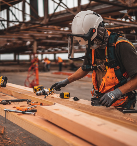 A construction worker measuring wood beams on a work bench