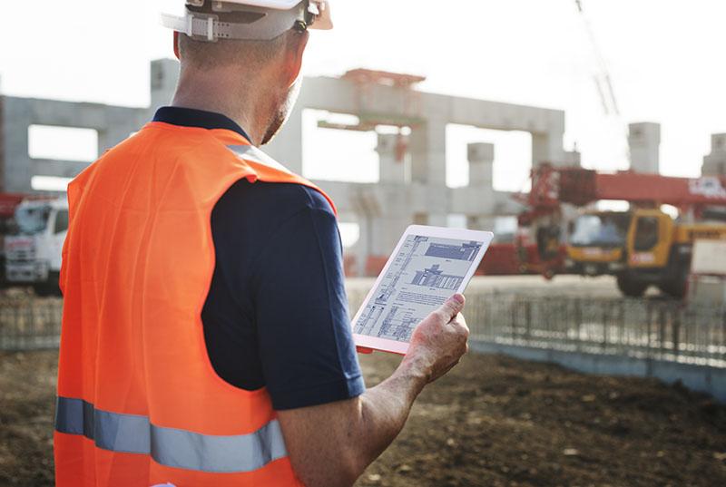 Construction worker with orange hi-vis vest onsite holding tablet