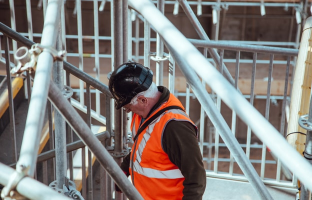 A foreman on a construction site inspecting scaffolding