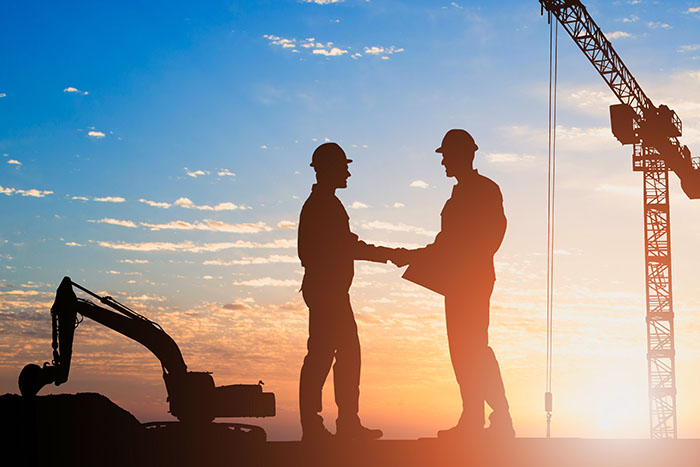 Silhouette of 2 male construction workers wearing hard hats shaking hands