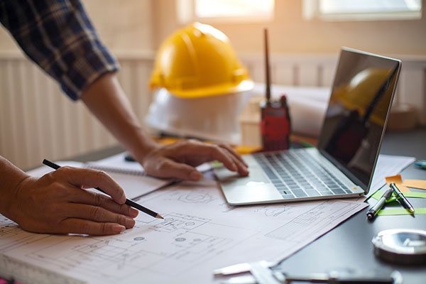 Construction worker leaning over desk with laptop and yellow helmet in background