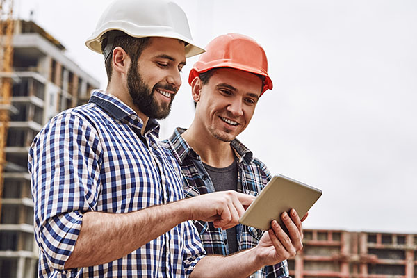 Two young and cheerful builders in protective helmets are using digital tablet and working while standing at construction site
