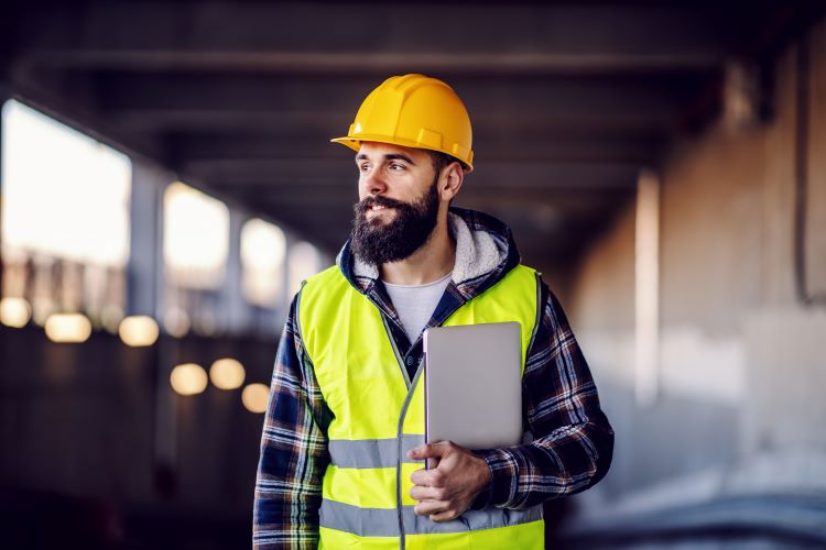 Bearded male construction worker with yellow hard hat and hi-vis vest carrying a tablet