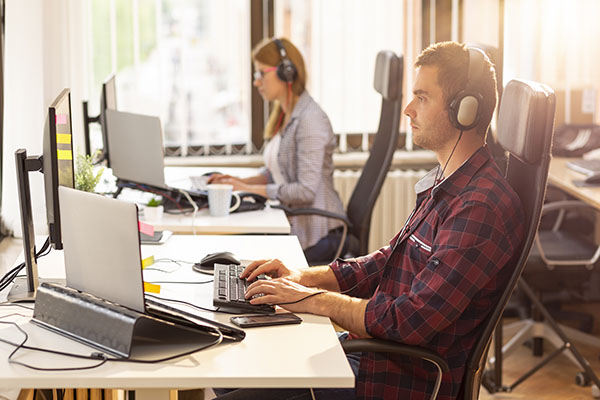 Office workers sitting at desks in front of laptops with headphones on