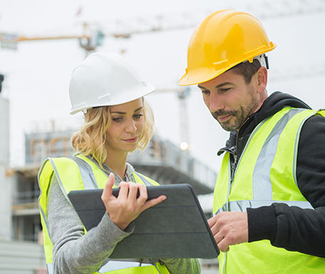 Male and female construction workers in yellow hi-vis vests and hard hats holding a tablet.