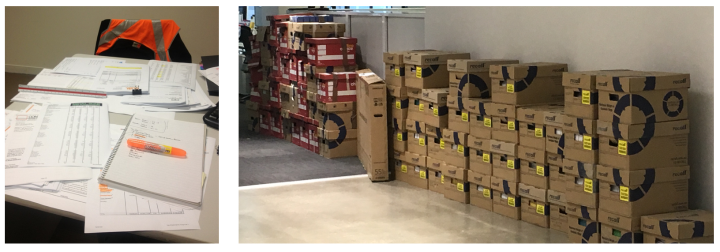 piles of boxes and paperwork against a wall