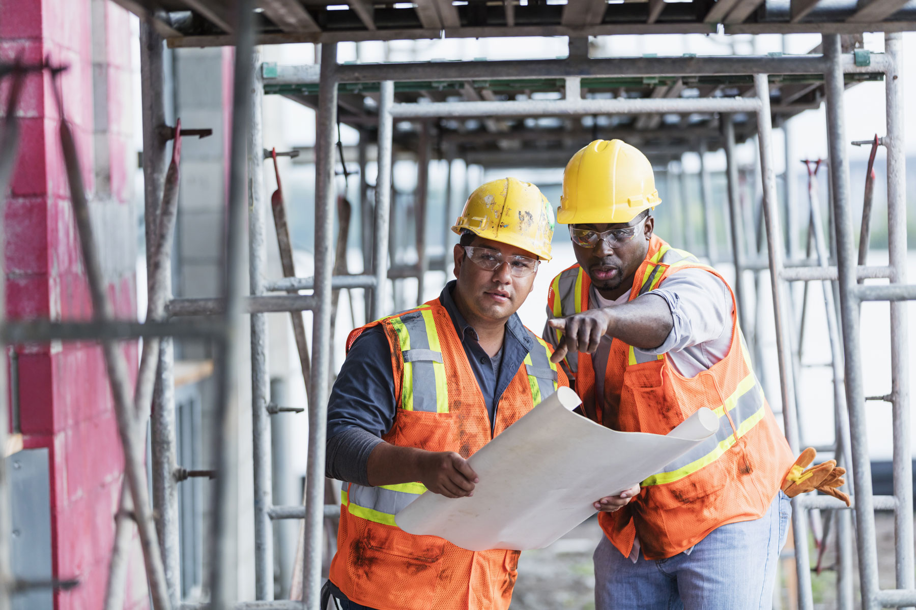 Younger hispanic construction worker learning on-the-job training from older african american worker.