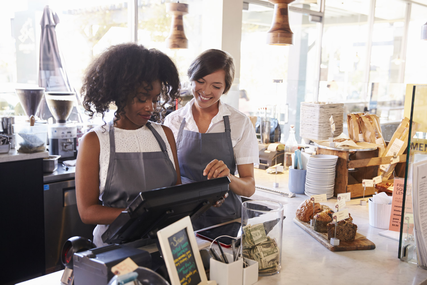 African american woman training younger asian american coffee shop worker