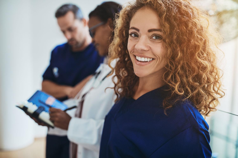 A happy hispanic nurse, happy she has her job.