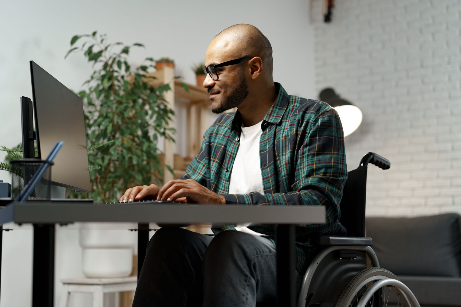 Disabled black man searching for job opportunities online while at home.