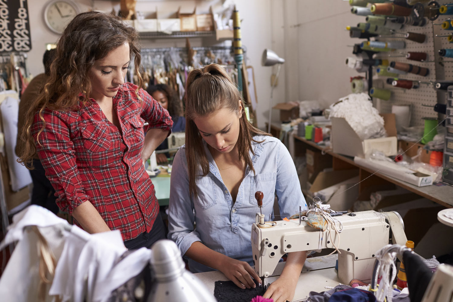 Young white seamstress being trained by older more experienced woman.