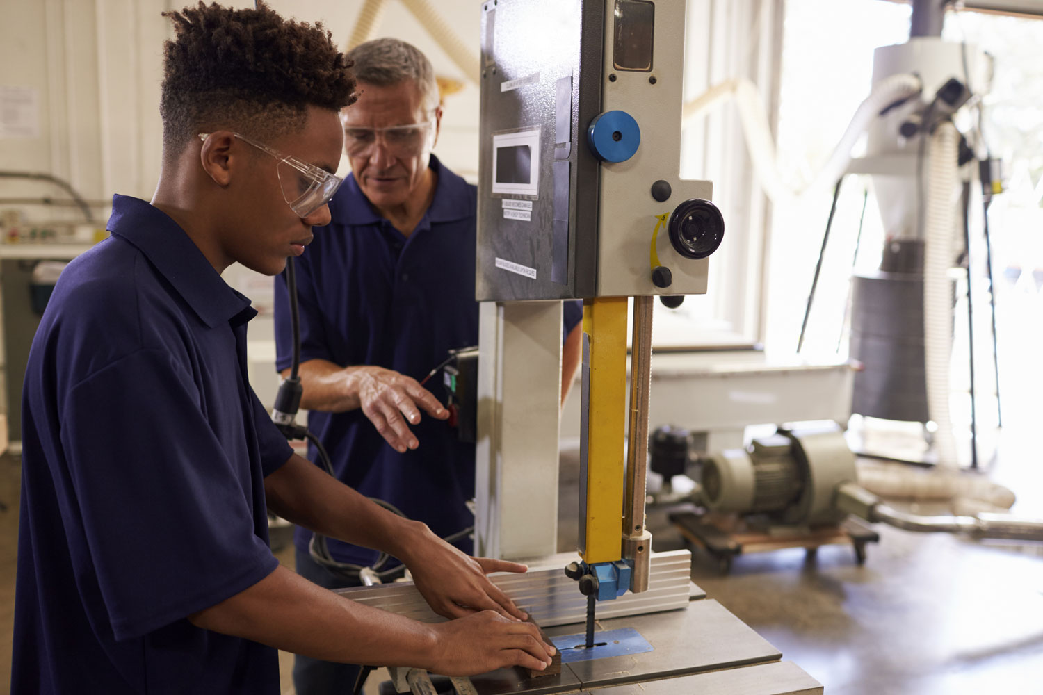 Older worker training young black man while on-the-job.