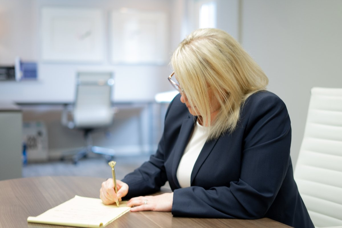 Debbie writing notes in conference room.