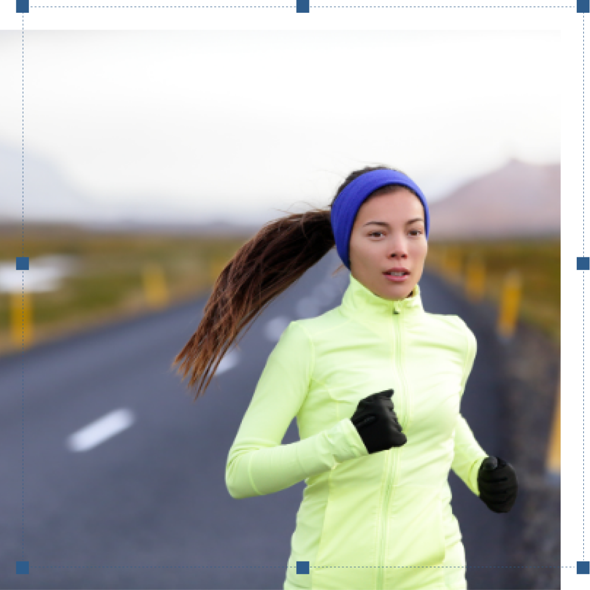 A woman runner ina light green jacket and pruple headband and blac gloves, on a long road with patches of snow in the side