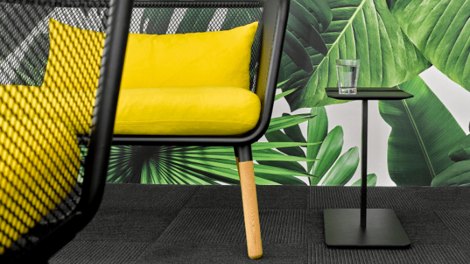A modern black metal chair with yellow custions.