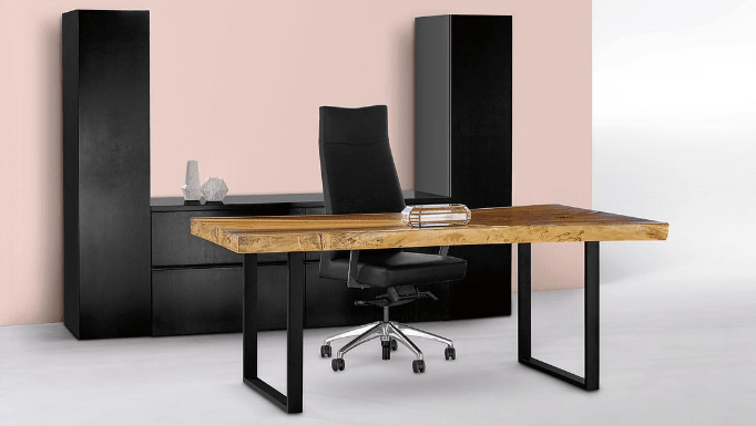 A thick, natural-wood desk in front of black cabinets