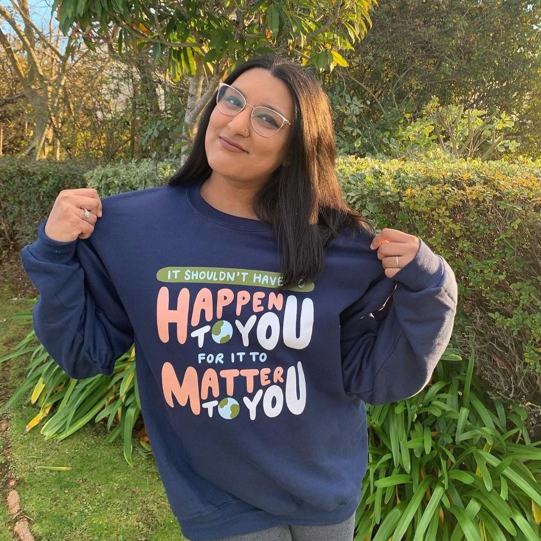 Girl wearing Oh Happy Dani X Bonfire merch, a navy sweatshirt