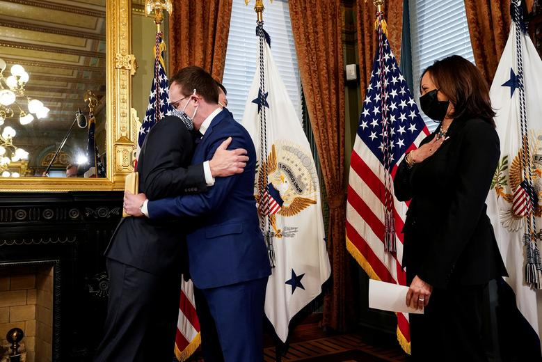 Pete Buttigieg hugs husband Chasten with Vice President Kamala Harris watching shortly after his confirmation. Photo from Reuters/Kevin Lamarque.