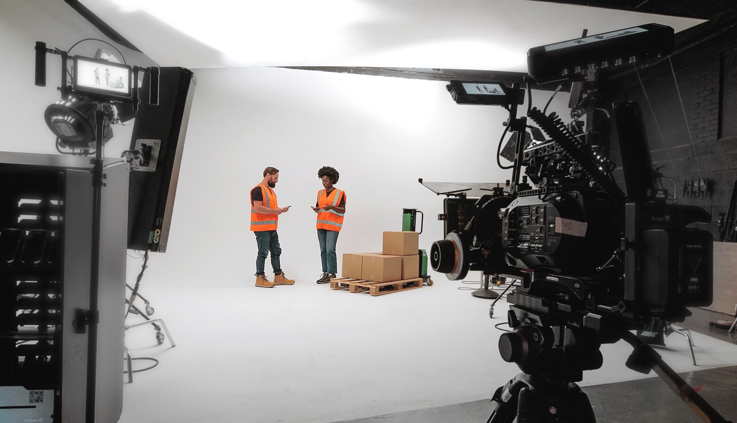 A man and a woman wearing hi-vis jackets on a film set with a camera