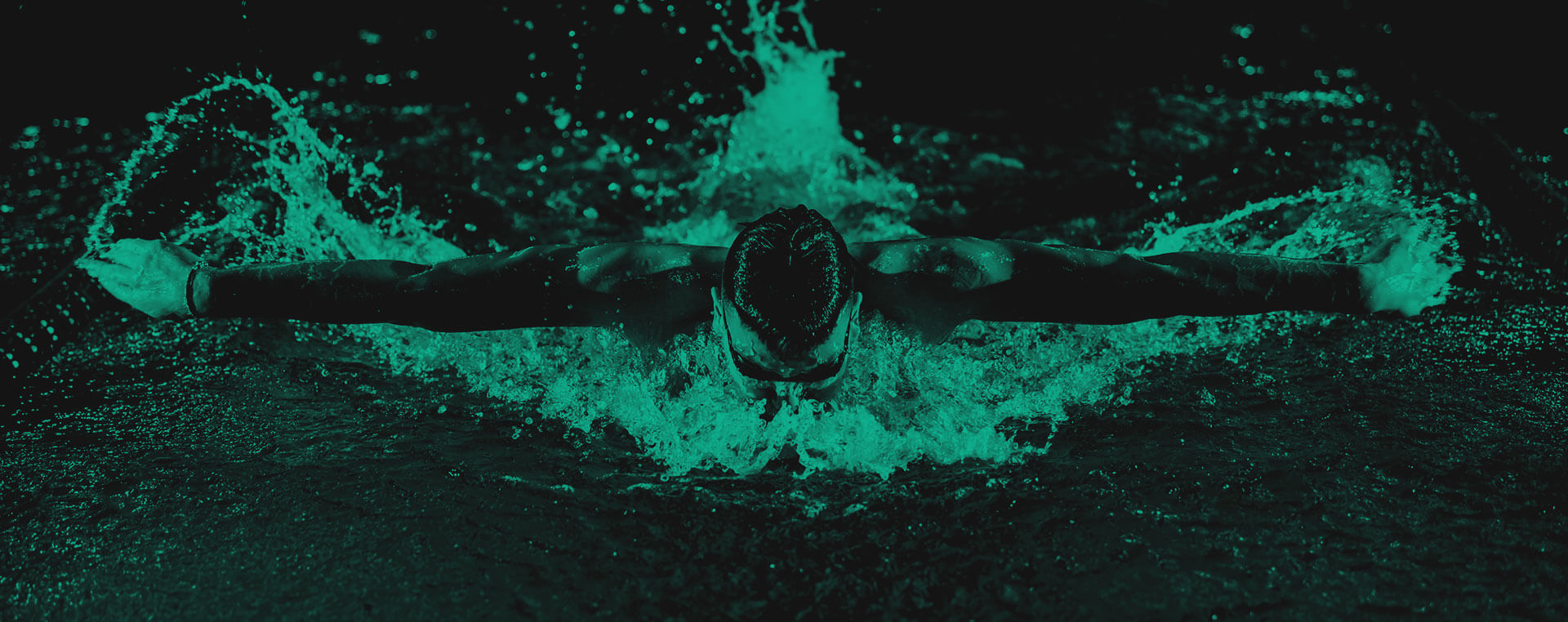 Green and black background image with a man swimming and facing the camera