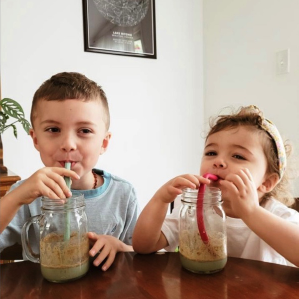 Two young kids enjoying their Super Greens smoothies