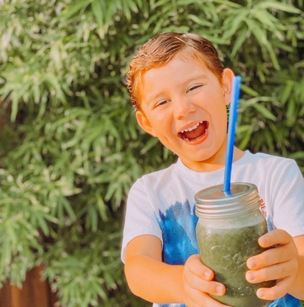 Very happy young boy enjoying a Super Green smoothie