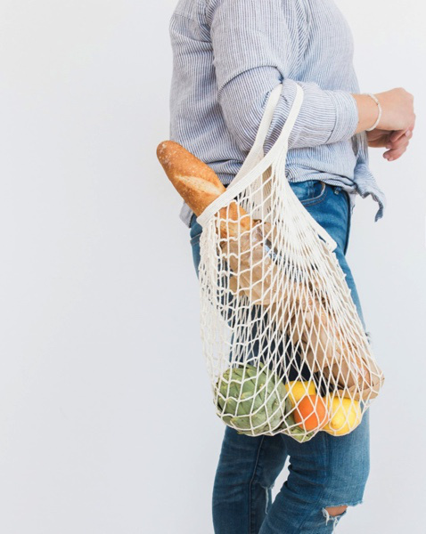 Woman holding a reusable grocery bag with produce inside