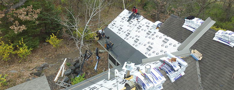 Aerial view of Keyprime workers installing new asphalt shingles on top of a multi-tiered residential home in the Twin Cities