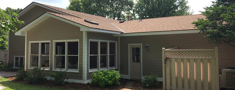 Back of home with vinyl siding, sunroom & door leading to backyard. Keyprime installs vinyl, steel, wood & cement siding