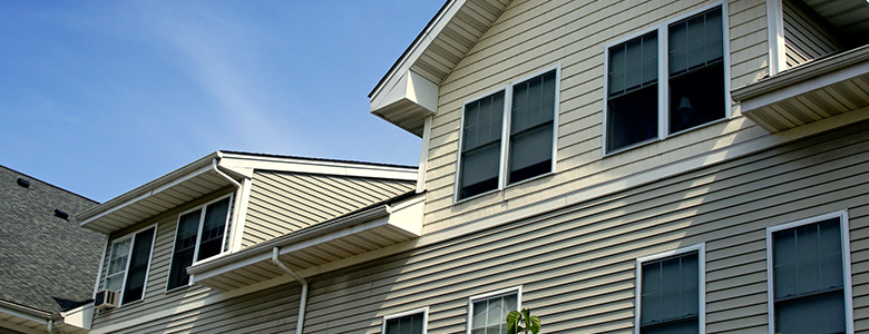 Partial view of a home with vinyl siding in half yellow, half beige with multiple windows. Keyprime does siding repair in MN