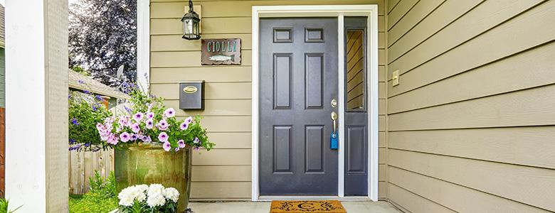 Entrance of home with flowers, rug & navy blue front door. Keyprime Roofing installs patio doors, entry doors & storm doors