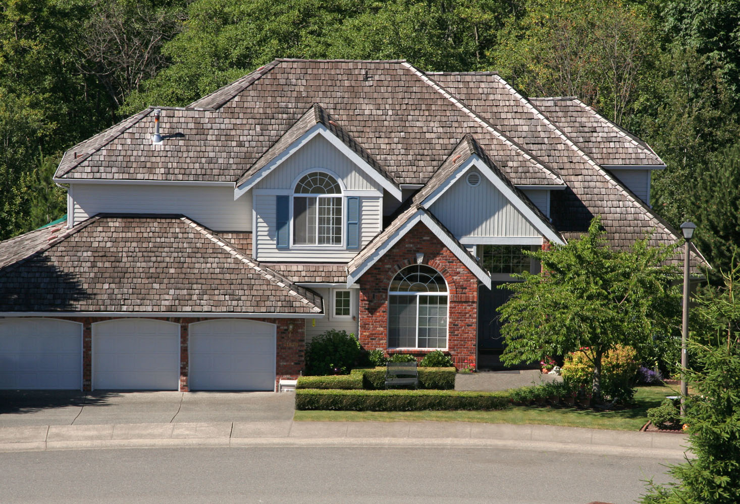 Home with 3-stall garage, covered entryway, manicured lawn & large cedar shake roof Keyprime: cedar shake roofing company
