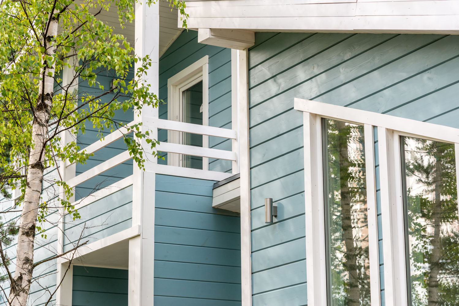Portion of home with light blue siding & white trim windows. Keyprime installs your windows, doors & siding to your liking