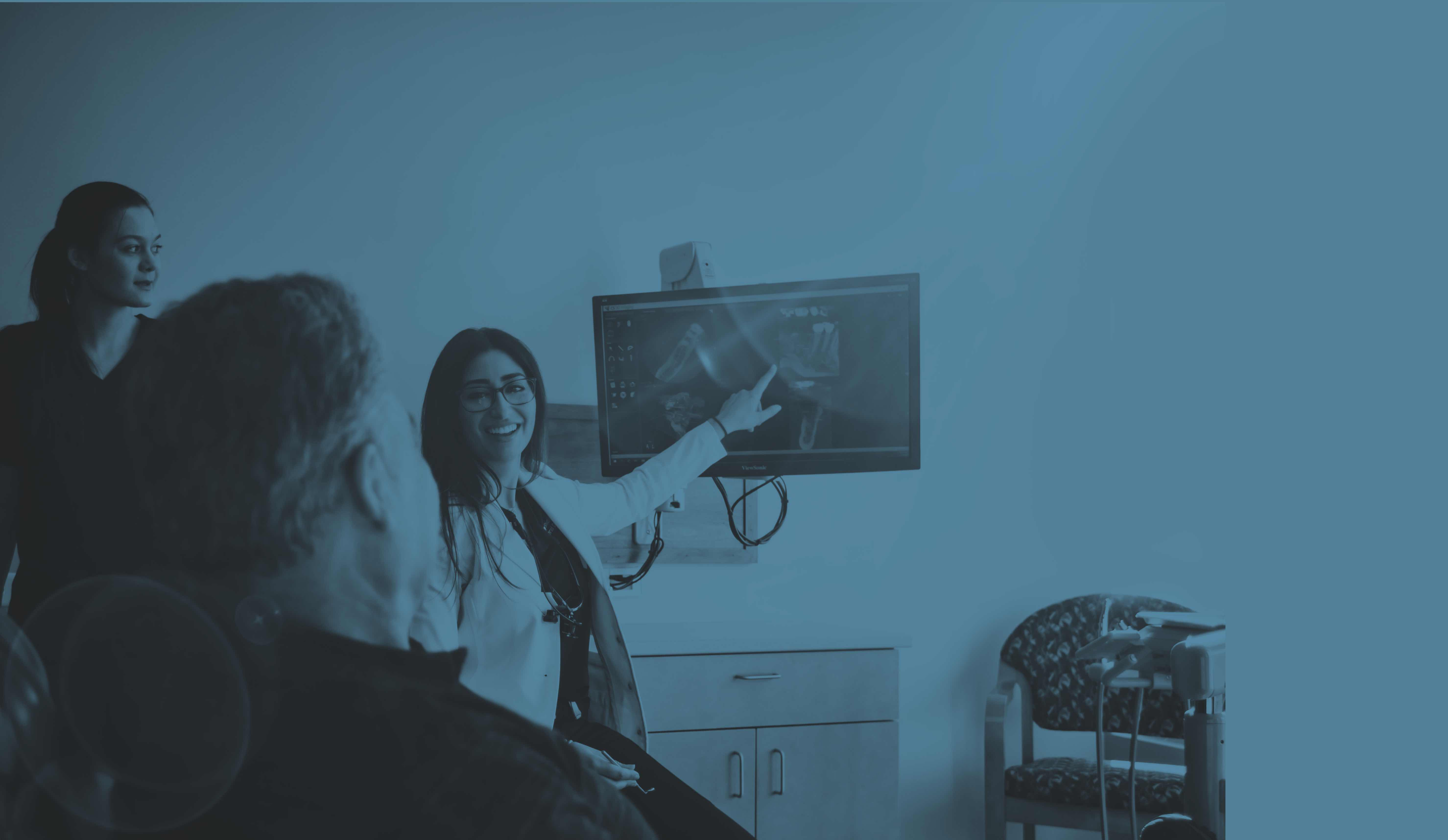 Photo of Englewood dentist Sahel Khorshidian DDS pointing at a dental x-ray image on a large screen