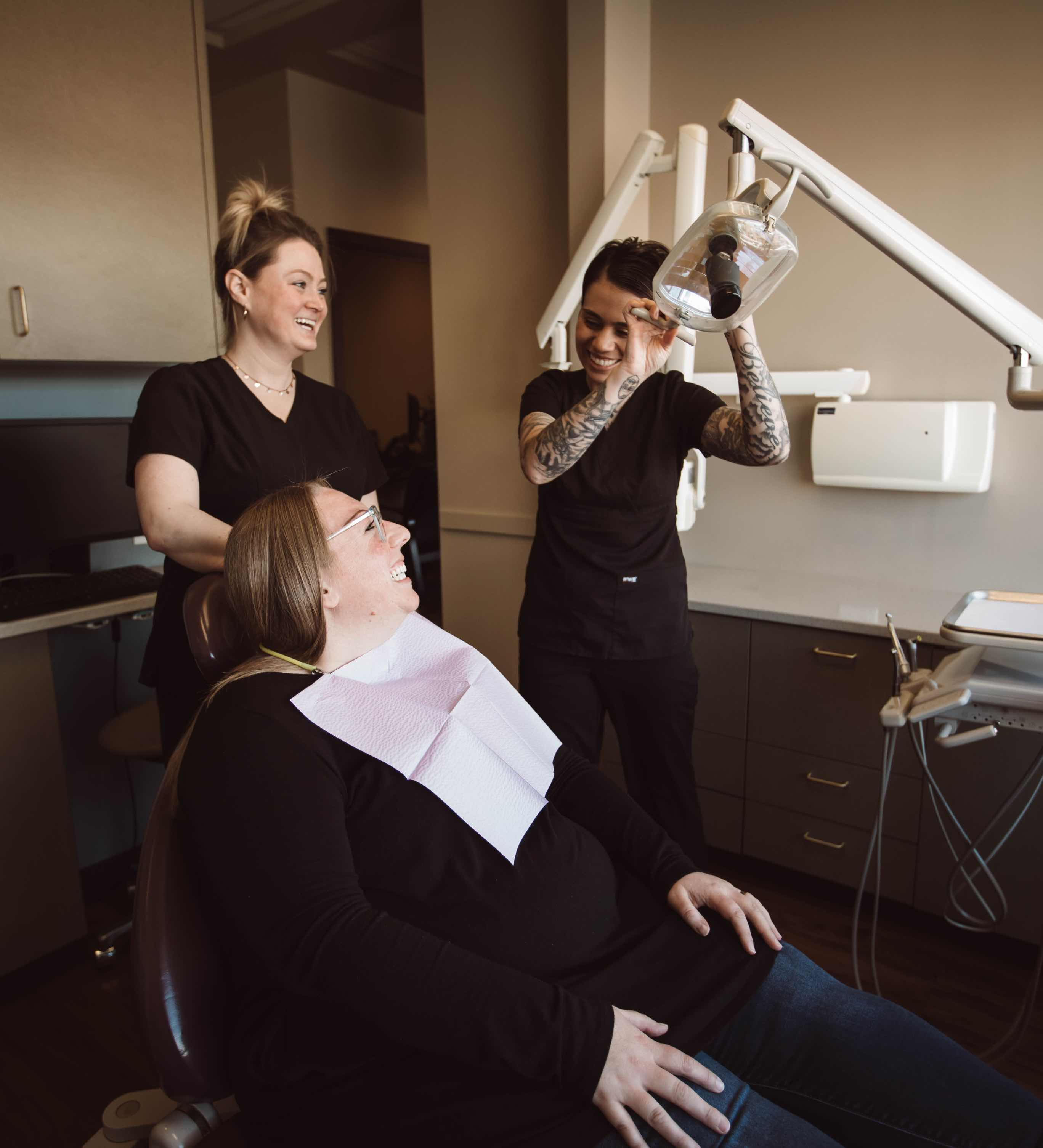 Photo of a patient sitting in a dental chair beside two team members