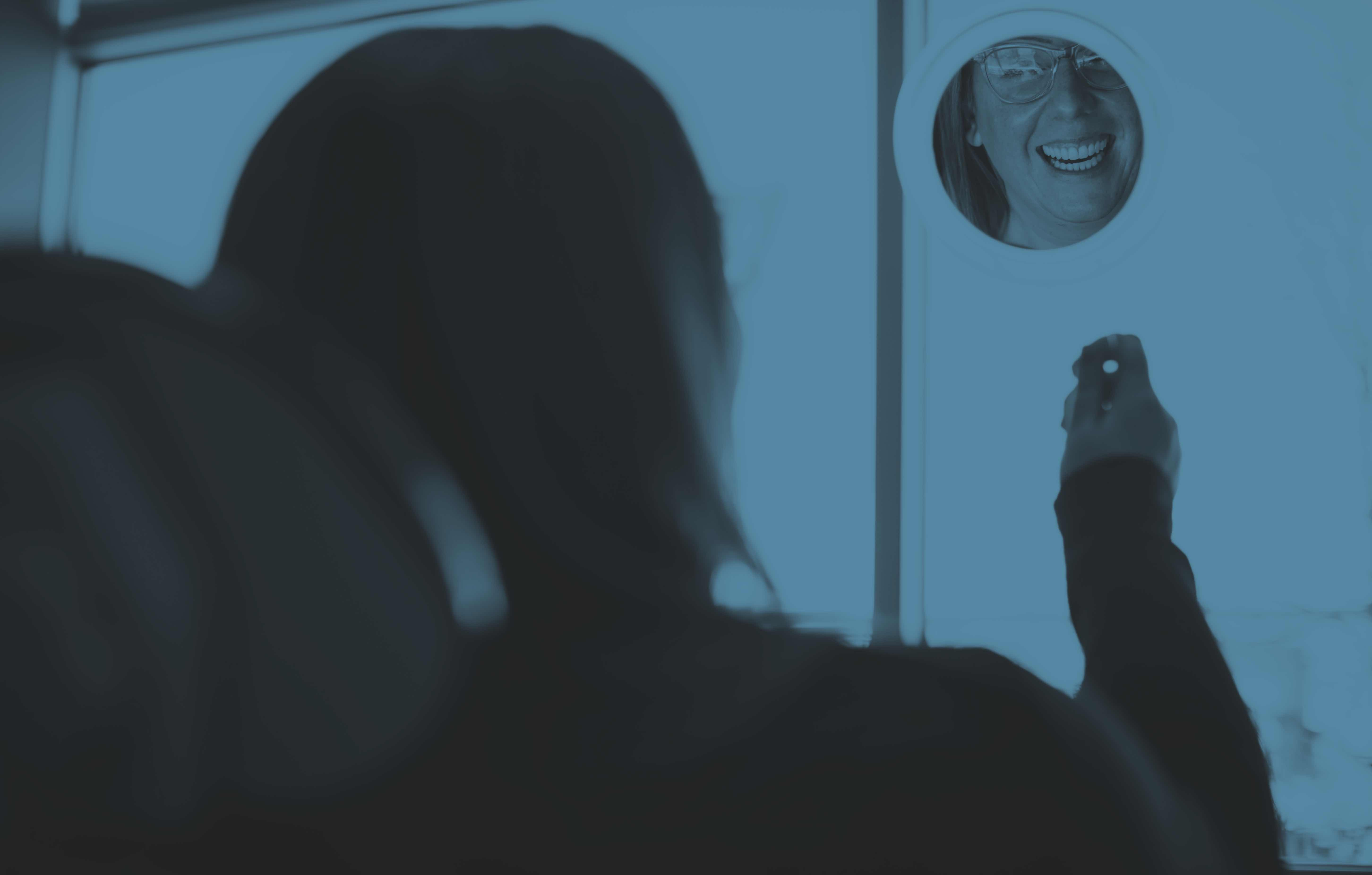 Photo of a dental patient looking at her smile in a mirror