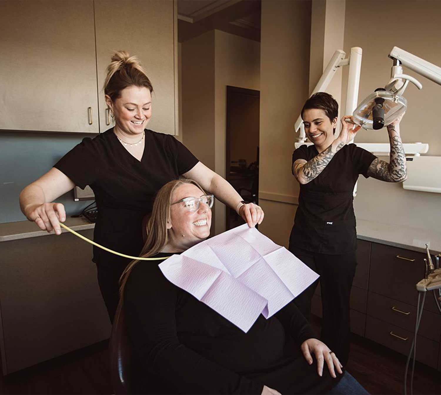 Photo of a patient sitting in a dental chair getting ready for her exam to start