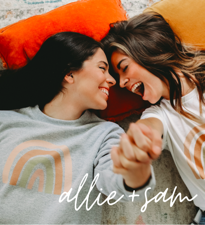 Allie + Sam holding hands and touching foreheads, wearing Allie + Sam official merch with Bonfire