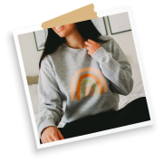 Allie looking cosy in Rainbow Love heather grey sweatshirt while sitting on bed, wearing Allie + Sam official merch with Bonfire