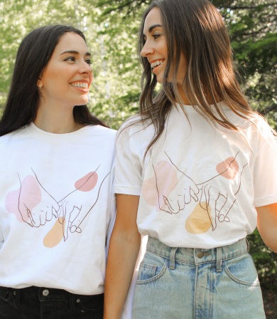 Allie + Sam standing together in the woods, wearing Allie + Sam official merch with Bonfire