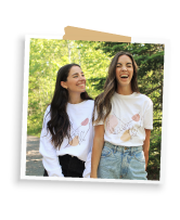 Sam wearing her Pinkie Promise white crewneck sweatshirt looking at Allie laughing wearing her Pinkie Promise unisex tee in white, official Allie + Sam merch with Bonfire