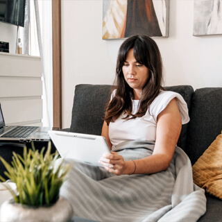 woman sitting on a sofa using a tablet