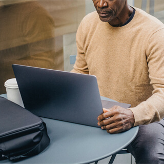 man sitting at a table using his laptop with a cup of coffee