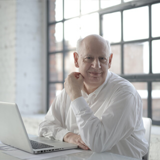 man sitting at a table in front of a laptop