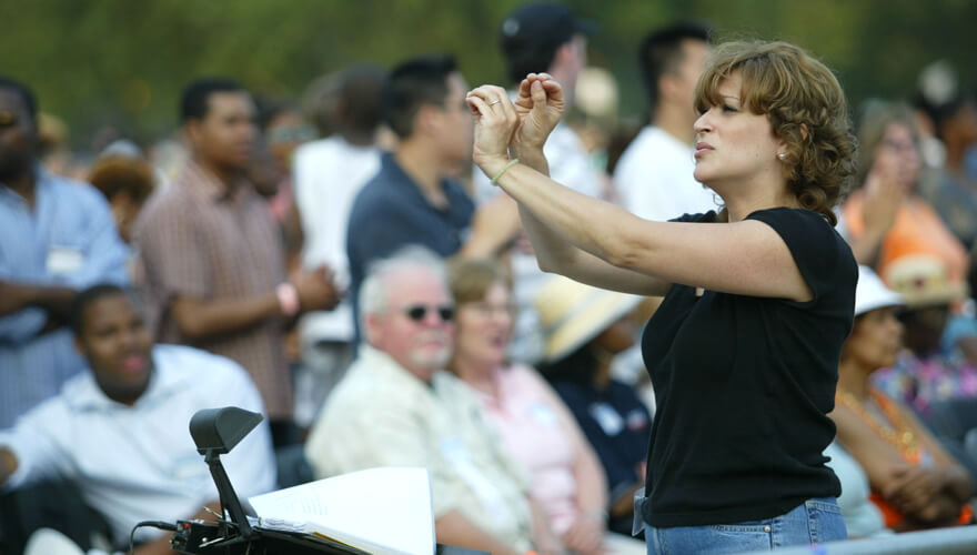 Woman signing to an audience at an outdoor event