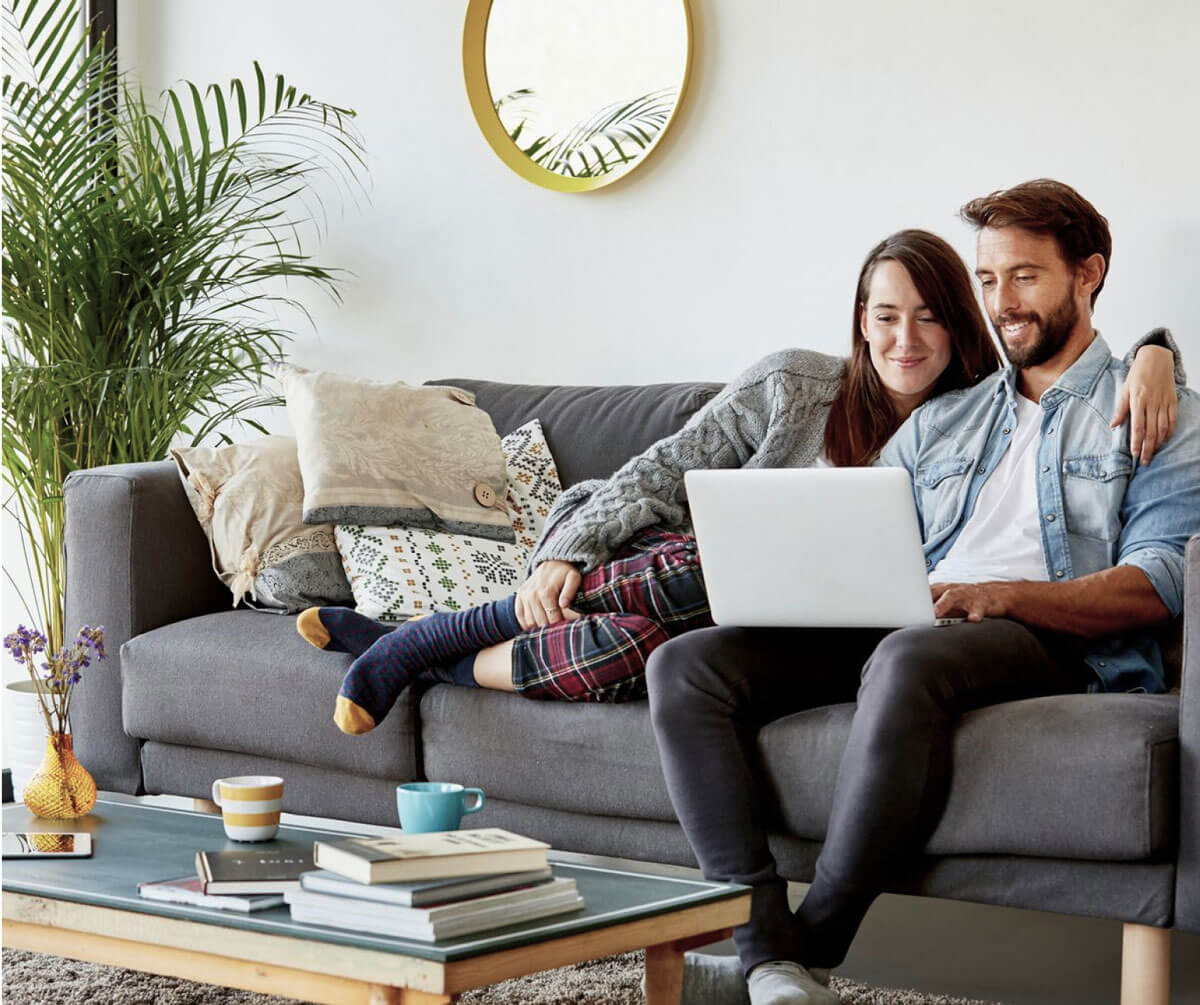 Man and woman sitting on a couch looking at a laptop while smiling