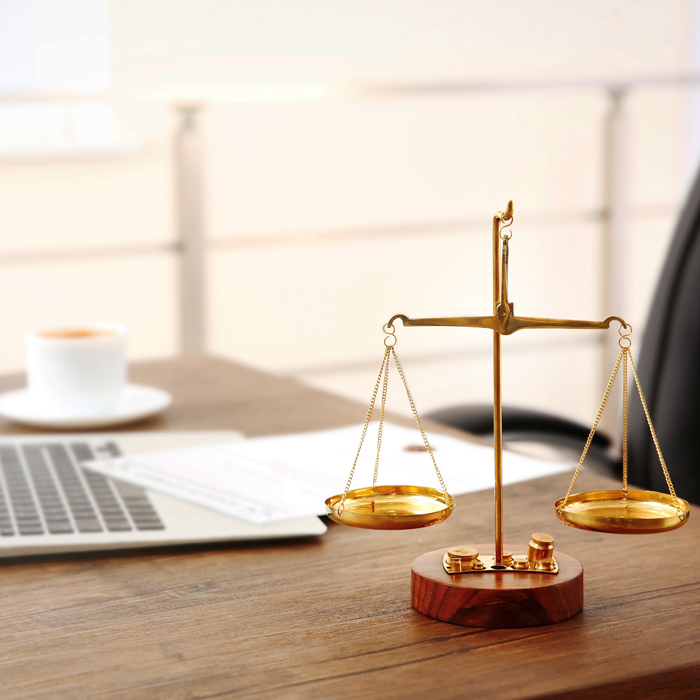 Desk with a laptop and scales of justice